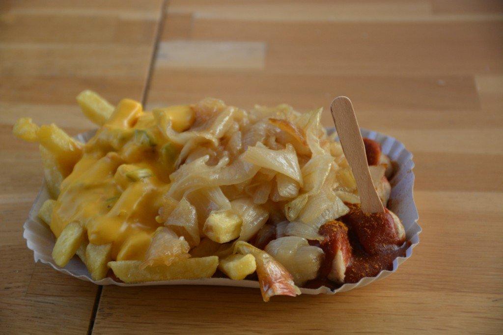 Currywurst mit Schmorzwiebeln und Pommes mit scharfer Käsesoße und Jalapenos bei der Wursterei Berlin