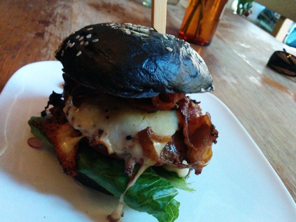 Burger mit schwarzem Bun, doppelt Bacon, weißer BBQ-Soße, 200 g Fleisch in der Fetten Kuh Köln
