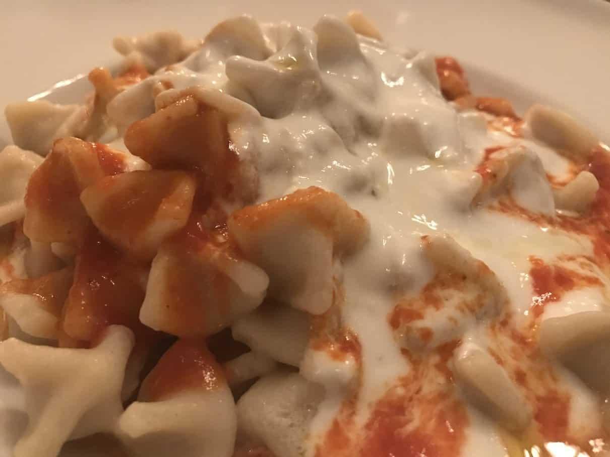 Nahaufnahme der Manti - Hackfleisch gefüllte Maultaschen nach türkischer Art mit Knoblauchjoghurtsauce und Butter im Taverna Yol Stuttgart