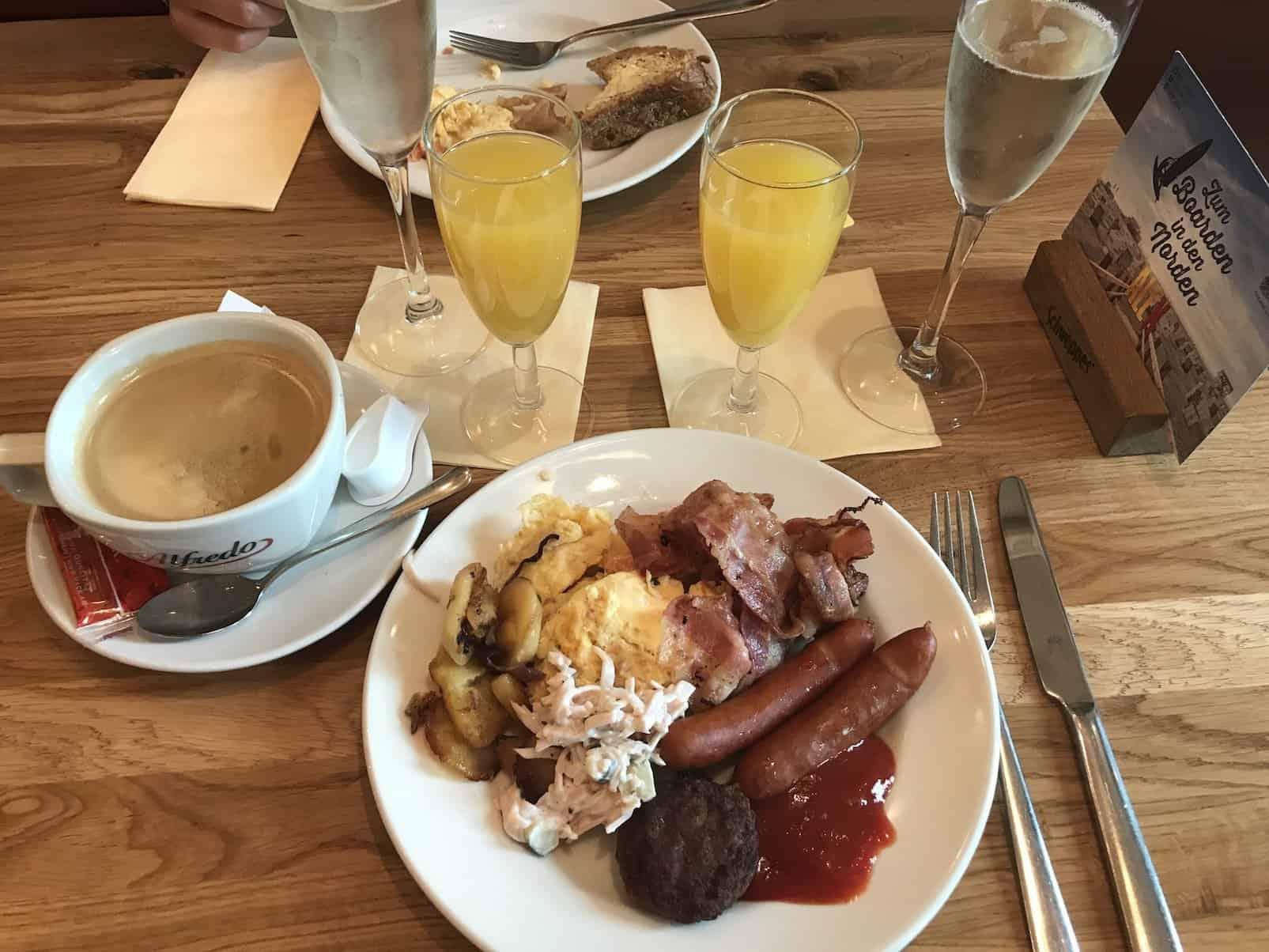 Mein erster Frühstücksteller mit Ei, Bratkartoffeln, Speck, Würstchen, Frikadelle - und Wurstsalat vom Frühstücksbuffet im Alex am Potsdamer Platz
