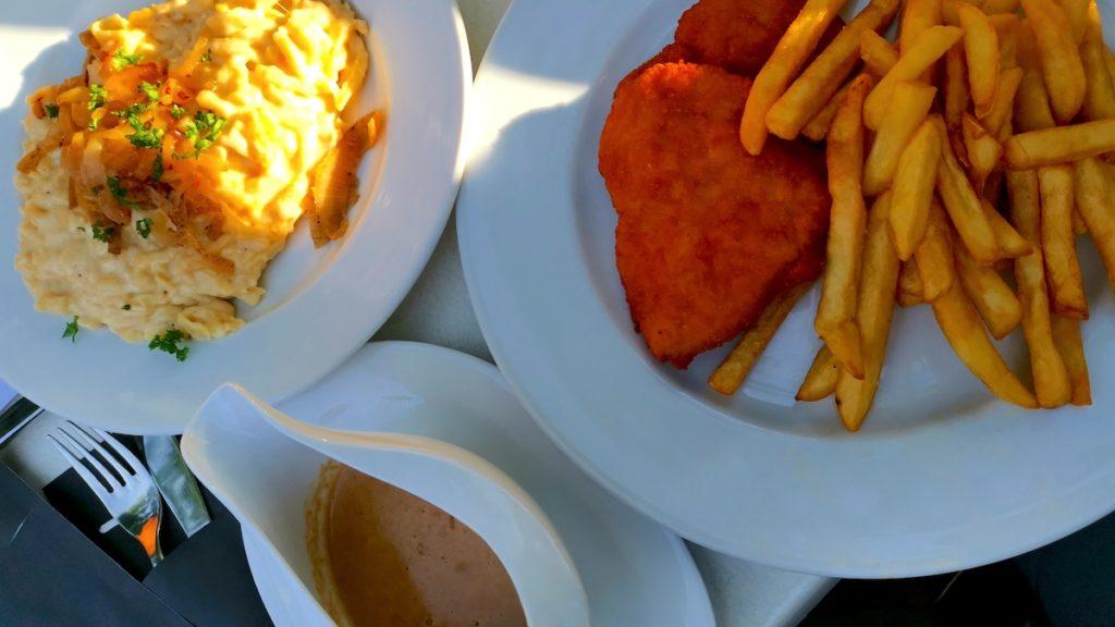 Rechts Schnitzel mit Pommes, links Kässpätzle, vorne Rahmsosse